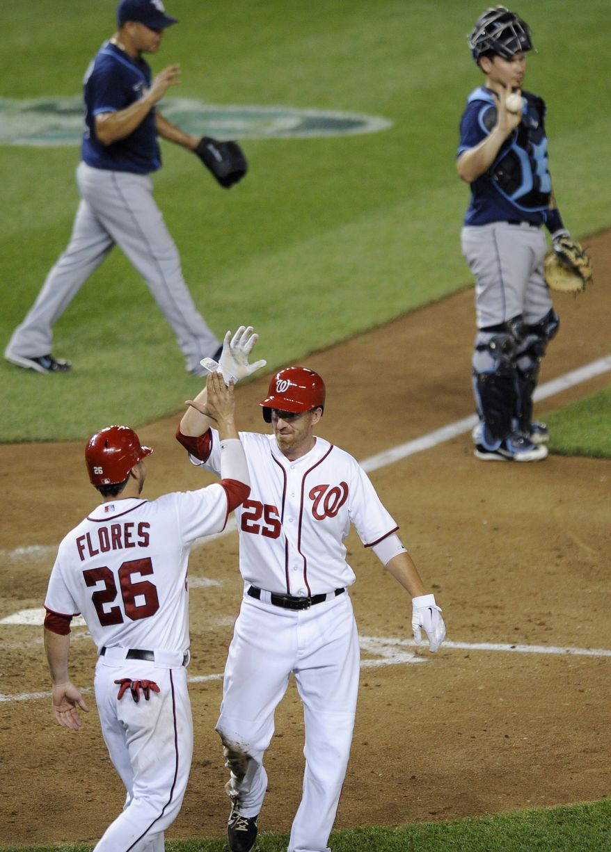 Washington Nationals' Adam LaRoche (25) and Jesus Flores (26) celebrate after they both scored on a double by Danny Espinosa during the sixth inning of a baseball game against the Tampa Bay Rays, Thursday, June 21, 2012, in Washington. At top right is Tampa Bay Rays catcher Jose Lobaton. The Nationals won 5-2. (AP Photo/Nick Wass)