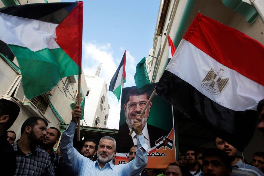 Ismail Haniyeh, prime minister of the Hamas-ruled Gaza Strip, waves the Palestinian and Egyptian flags Sunday in Gaza City during celebrations of the victory of Mohammed Morsi in neighboring Egypt's presidential elections. (Associated Press)