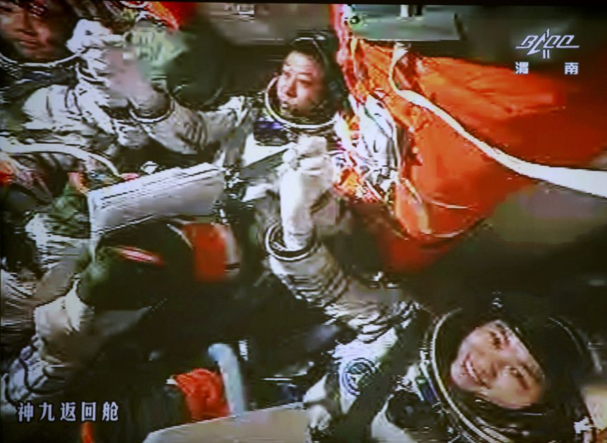 ** FILE ** In this image made from the monitor at the Beijing Aerospace Flight Control Center and released by China's Xinhua News Agency, Chinese astronauts Jing Haipeng (center), Liu Wang (left) and Liu Yang celebrate aboard the Shenzhou-9 spacecraft after a successful manual docking between the spacecraft and the Tiangong-1 lab module on Sunday, June 24, 2012. (AP Photo/Beijing Aerospace Control Center via Xinhua)