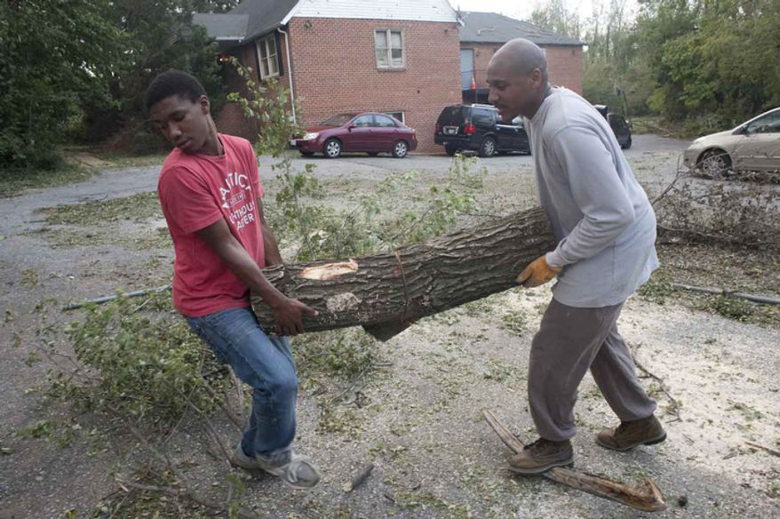 Dangelo Henderson, 15,  from Greenbelt,  helps Carl Clark, from Capital Heights, move a tree truck on Sunday, June 24, 2012, in  Bladensburg, Md.  (Raymond Thompson/The WashingtonTimes)