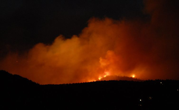 The evening sky glows orange with smoke and flames as the Waldo Canyon Fire rages west of the Garden of the Gods near Colorado Springs, Colo., on Saturday, June 23, 2012. ( AP Photo/Bryan Oller)