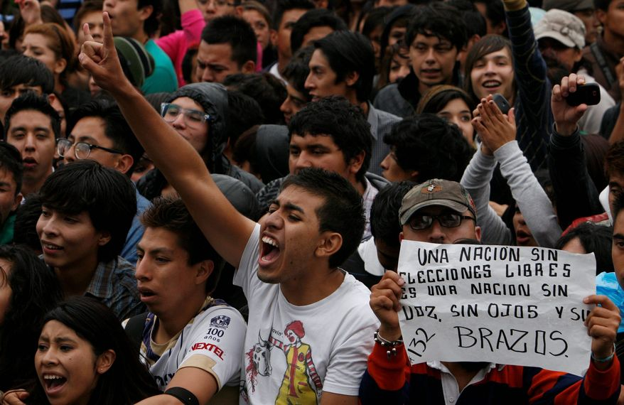 """Youths attend a music festival in support of the student movement #YoSoy132, or """"I am 132"""" in Mexico City's Zocalo plaza, Saturday June 16, 2012. #YoSoy132 is the name of a university movement that rejects the possible return of the old ruling Institutional Revolutionary Party (PRI) ahead of Mexico's July 1 presidential election. The sign at right reads in Spanish """"A nation without free elections is a nation without voice, without eyes and without arms."""" (AP Photo/Marco Ugarte)"""