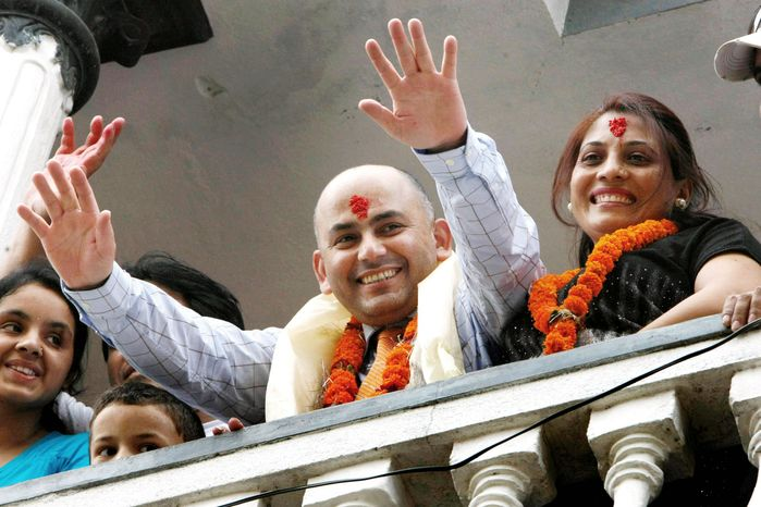 Govinda Prasad Mainali, with his wife Radha (right), waves upon his arrival at his home in Katmandu, Nepal, on June 16. Mainali, 45, spent 15 years in a Japanese jail for the murder of a Japanese woman in 1997. He was freed by the Tokyo High Court based on new DNA testing that cleared him. (Associated Press)