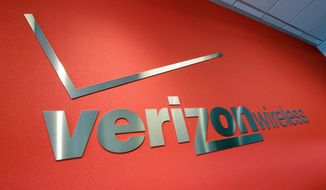 "A watchdog group said that Verizon is trying to ""buy off"" T-Mobile through a sale-and-swap agreement. Verizon has been seeking approval from regulators on a bigger spectrum deal with cable companies and another wireless carrier. (Associated Press)"