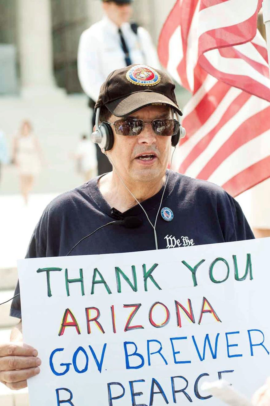 Ron Kirby, of Alexandria, holds a sign thanking Arizona's governor for the state's immigration law, which was the subject of a Supreme Court ruling on Monday. (Raymond Thompson Jr./The Washington Times)