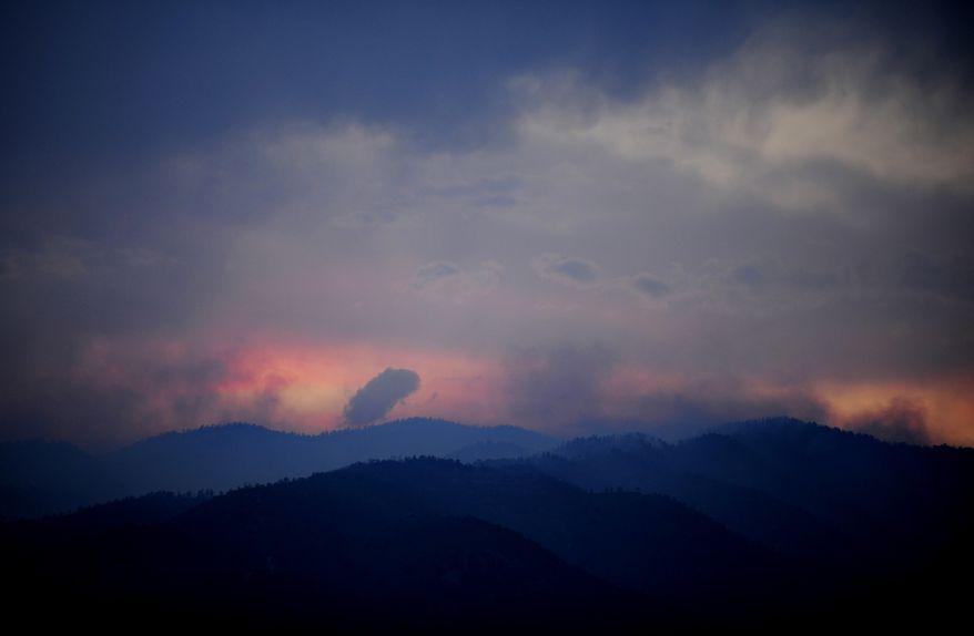 Wildfires burn west of Colorado Springs, Colo. on Sunday, June 24, 2012, as the sun sets. (AP Photo/Colorado Springs Gazette, Susannah Kay)