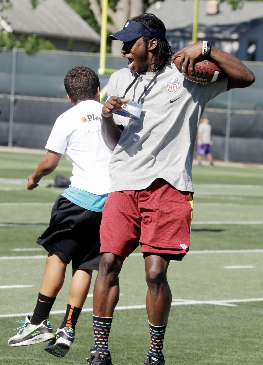 Robert Griffin III celebrates with a youngster during a youth football camp at the Cleveland Browns' training facility in Berea, Ohio. Griffin recently was revealed to be the target of an extortion attempt. (Associated Press)