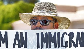 Gonzalo Hernandez stands outside a Scottsdale, Ariz., resort Monday protesting GOP presidential hopeful Mitt Romney, who was speaking inside, and Arizona's immigration law, a key part of which was upheld by the Supreme Court. (Associated Press)