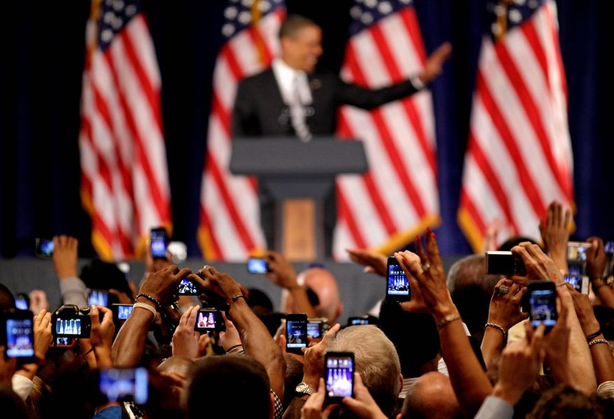 Cameras snap President Obama as he waves from the lectern at a fundraising event Tuesday in Atlanta. The president has been pushing hard for campaign contributions. (Associated Press)