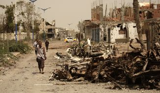 **FILE** A Yemeni man walks June 14, 2012, past cars destroyed during fighting with al Qaeda militants in Zinjibar, Yemen. (Associated Press)