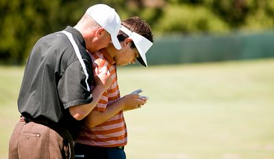Bill Schellenberg, left, and Beau Hossler, right, watch a video Schellenbenberg took on his cell phone of Hossler hitting balls on the range at Congressional Country Club during the AT&T National on Tuesday, June 26, 2012.  Schellenberg is both Hossler's caddy and godfather.  (Ryan M.L. Young/The Washington Times)