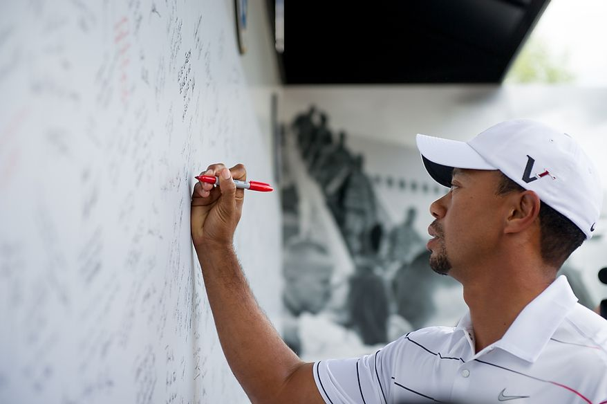 "Tiger Woods signs a ""We Salute Our Heroes"" wall near the eighteenth hole before the AT&T National golf tournament, set to begin on Thursday, held at Congressional Country Club, Bethesda, Md., Tuesday, June 26, 2012. The wall will be available for pros and fans to sign all week and will then be distributed for service members to be able to view in a variety of military locations. (Andrew Harnik/The Washington Times)"