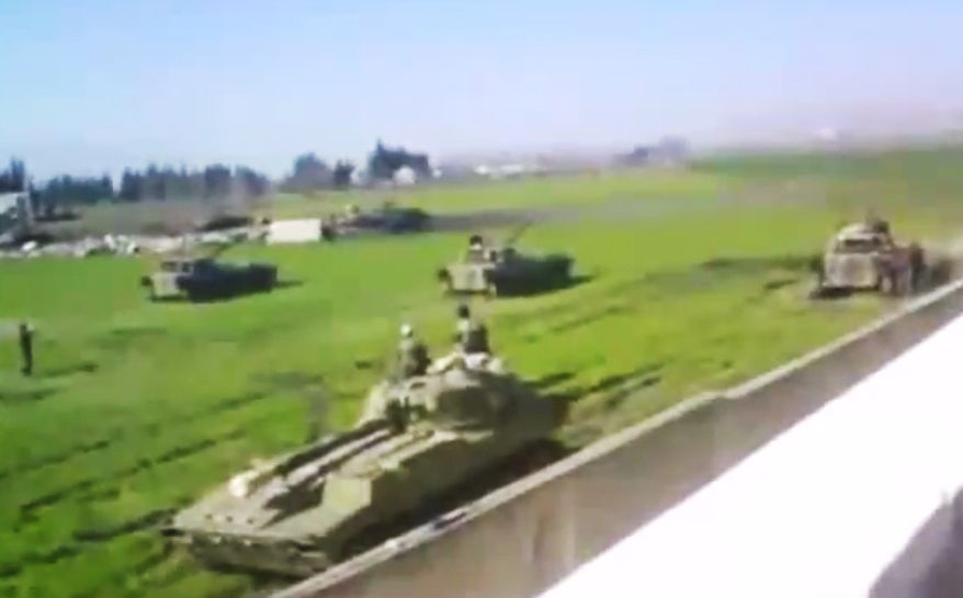 This image made from amateur video released by the Shaam News Network and accessed on Sunday, June 24, 2012, purports to show Syrian military tanks in Hama, Syria. (AP Photo/Shaam News Network via AP Video)