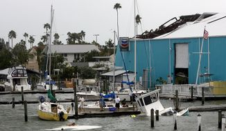 Swimmers and a diver work to save sunken boats at Pass-a-Grille, Fla. Marina on June 26, 2012. High winds and heavy rains spawned by the approaching Tropical Storm Debby caused the damage. (Associated Press/Tampa Bay Times)