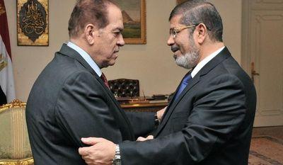 Kamal el-Ganzouri (left), Egypt's caretaker prime minister, shakes hands with Egyptian President-elect Mohammed Morsi in Cairo on Monday, June 25, 2012. (AP Photo/Middle East News Agency)