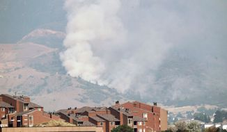 """A plume of smoke rises behind homes from the Waldo Canyon Fire west of Colorado Springs on Wednesday. """"It was like looking at the worst movie set you could imagine,"""" Gov. John Hickenlooper said after flying over the 9-square-mile fire late Tuesday. (Associated Press)"""