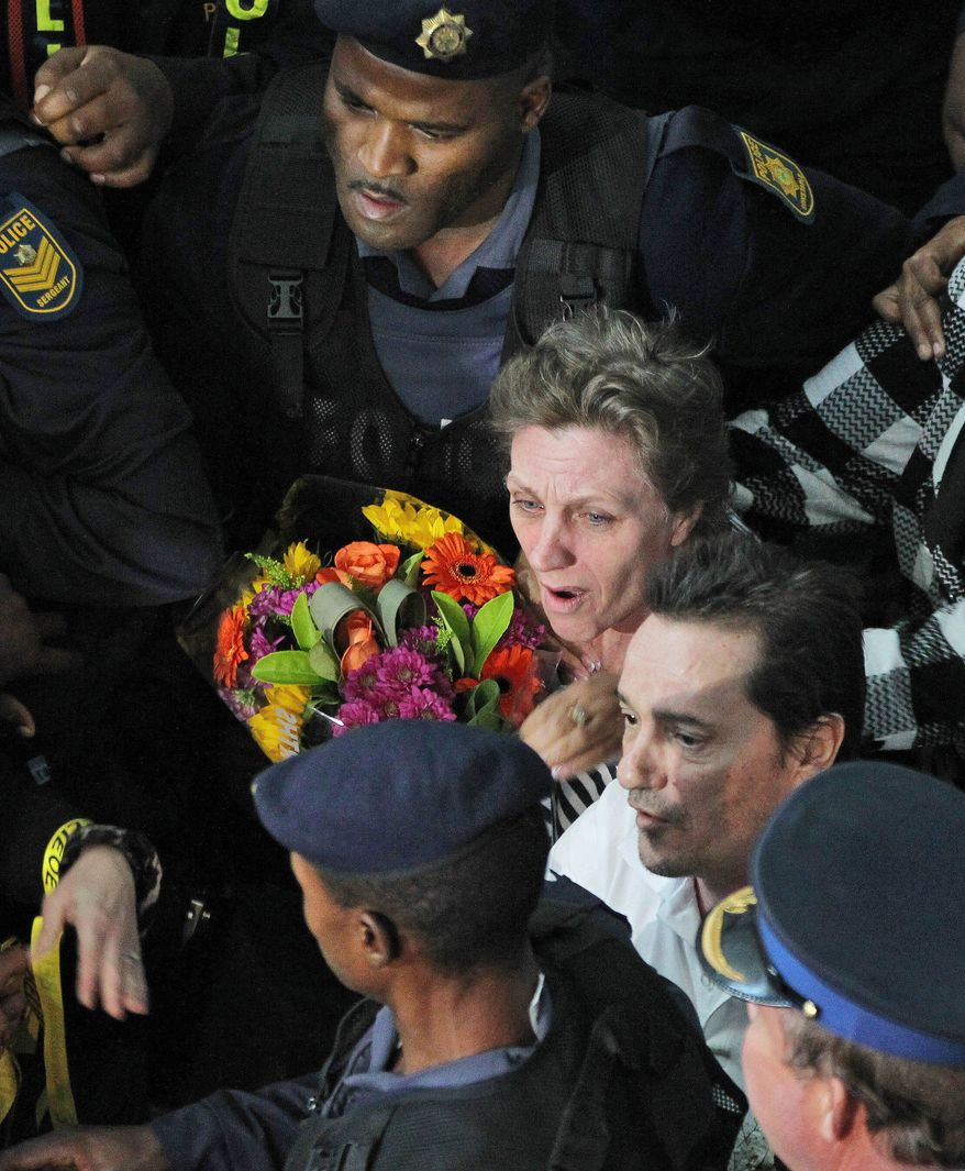 Deborah Calitz (center) and her partner Bruno Pelizzari (bottom center) are escorted June 27, 2012, by a police officer upon their arrival at the OR Tambo International Airport in Johannesburg. The couple was held hostage for 20 months after being kidnapped from a yacht by Somali pirates in October 2010. (Associated Press)