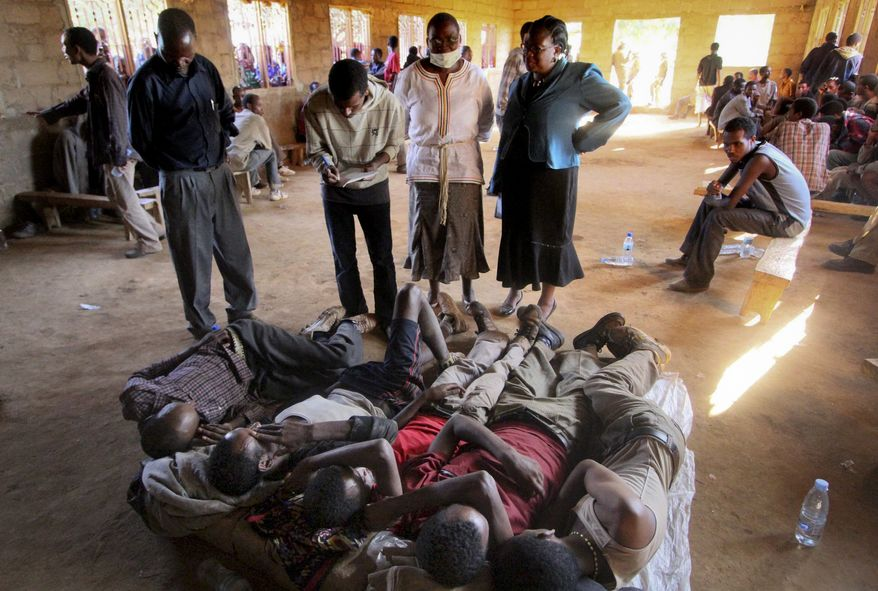 Tanzanian officials speak with survivors of an incident where more than forty people suffocated to death in a truck container near Chitego Forest, about 80 miles east of the capital Dodoma, in Tanzania. Tanzania lies on a smuggling route Africans use to travel to South Africa, where there are more economic opportunities. (Associated Press)