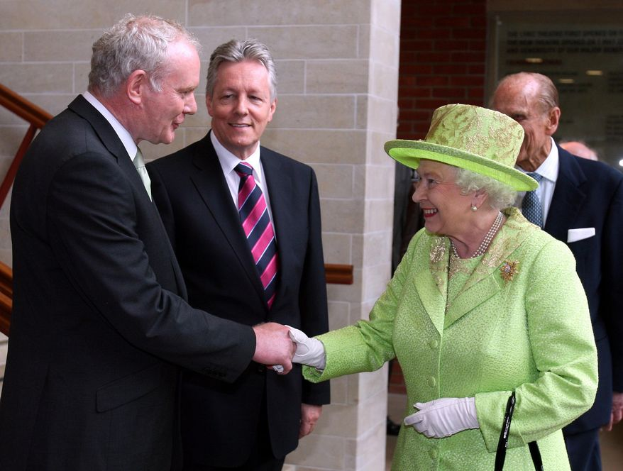 Britain's Queen Elizabeth II shakes hands with Northern Ireland Deputy First Minister Martin McGuinness, a former IRA commander, as First Minister Peter Robinson (center) looks on at the Lyric Theatre in Belfast, Northern Ireland, on Wednesday, June 27, 2012. Prince Philip, the queen's husband, is at right. (AP Photo/Paul Faith, Pool)