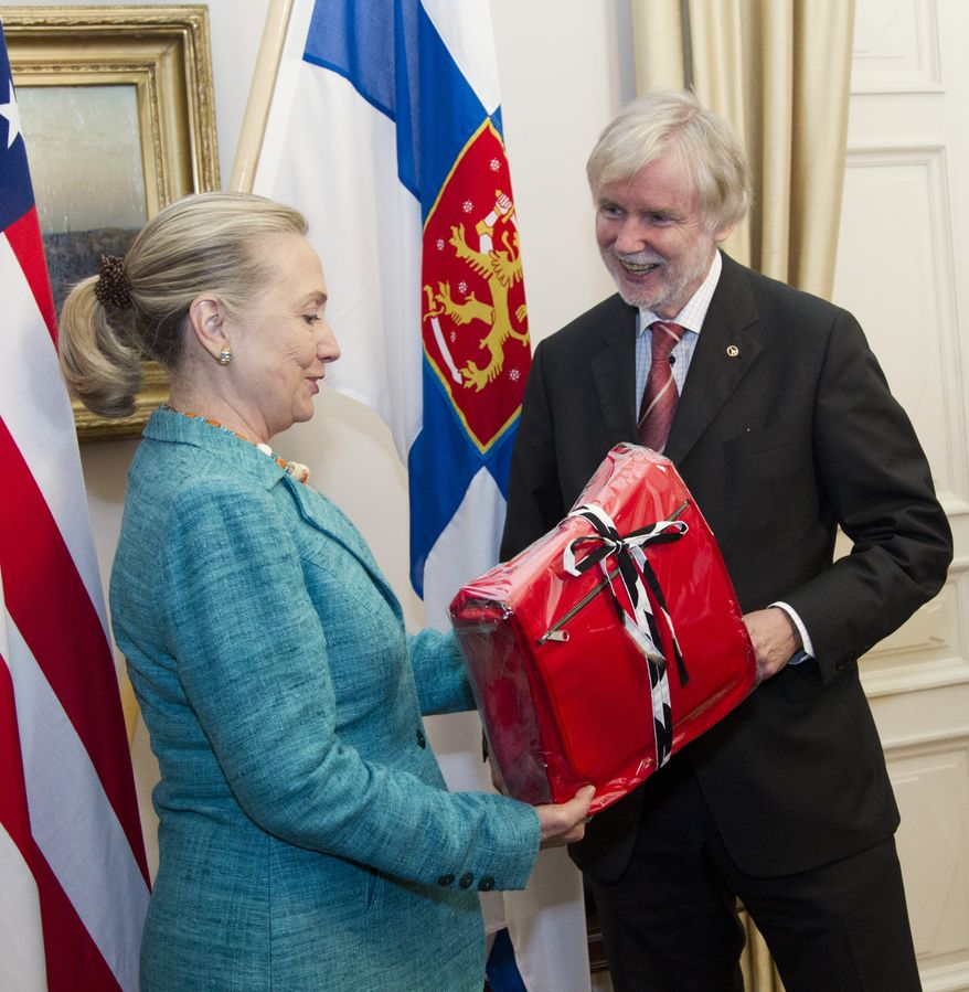 U.S. Secretary of State Hillary Rodham Clinton receives a gift June 27, 2012, from Finnish Foreign Minister Erkki Tuomioja at the Government Banquet Hall in Helsinki, Finland. (Associated Press)
