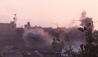 In this image made from amateur video released by the Shaam News Network and accessed on Tuesday, June 26, 2012, smoke rises from buildings following purported shelling in Homs, Syria. (AP Photo/Shaam News Network via AP Video)