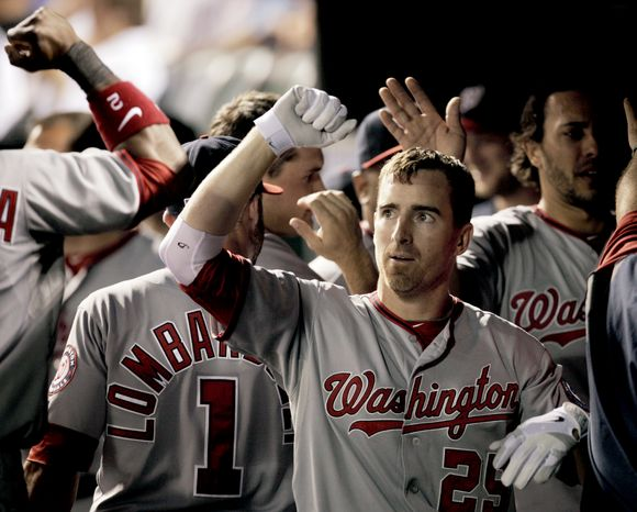 Washington Nationals' Adam LaRoche is congratulated in the dugout after his home run against the Colorado Rockies in the sixth inning of a baseball game in Denver, Tuesday, June 26, 2012. (AP Photo/Joe Mahoney)