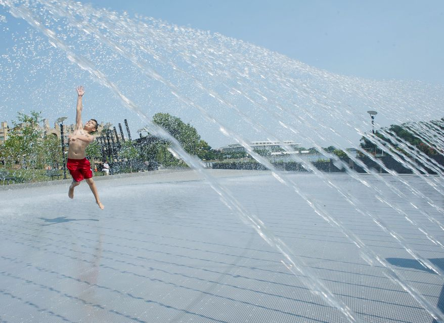 Declan Faris, 10, of Alexandria finds a great way to beat the heat while frolicking in the fountain at the Georgetown Waterfront Park on Thursday, June 28, 2012. (Barbara L. Salisbury/The Washington Times)