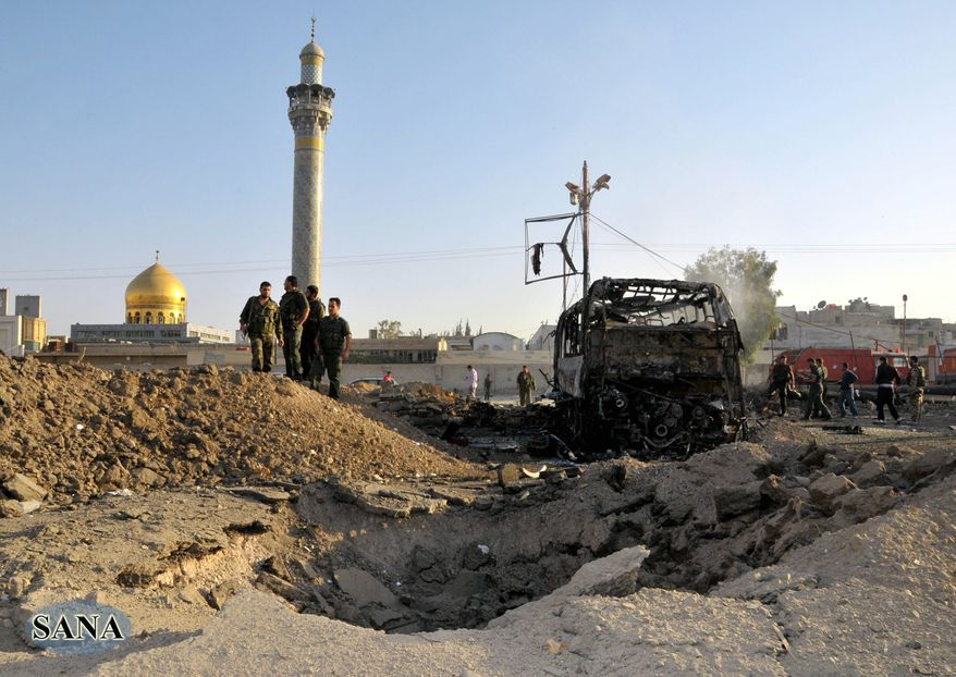** FILE ** In this photo released by the Syrian official news agency SANA, Syrian soldiers stand at the explosion site where a car bomb exploded near the shrine of Sayyida Zeinab, seen in the background, suburb of Damascus, Syria, Thursday, June 14, 2012. A car bomb exploded Thursday in a Damascus suburb that is home to a popular Shiite Muslim shrine, wounding at least two people, Syria's state-run news agency SANA reported, while activists said regime troops continued shelling rebellious areas in central Homs province. (AP Photo/SANA)