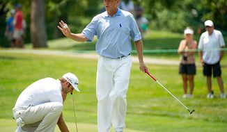 Davis Love III, center, waves to the crowd after sinking his putt as Dustin Johnson, left, sets up to putt on the eighth hole on the first day of the AT&T National golf tournament held at Congressional Country Club, Bethesda, Md., Thursday, June 28, 2012. (Andrew Harnik/The Washington Times)