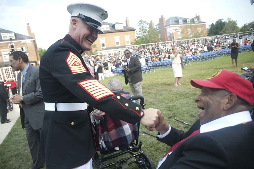 Robert Matthew Mason Jr, 87, from San Francisco,  and Sgt. Maj. Michael Barrett (cq) share a laugh during the Montford Pointe Marines Parade at the Marine Barracks Washington on Thursday, June 28, 2012, in Washington D.C. Approximately 20,000 African American Marine recruits where trained at Montford Pointe when the military was still segregated. The serving members received the Congressional Gold Medal for their service. (Raymond Thompson/The Washington Times)