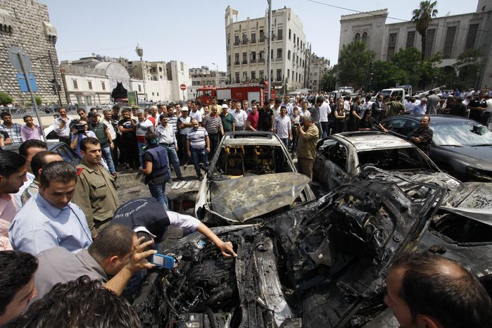 Syrians inspect burned cars June 28, 2012, at the site of a blast in the Syrian capital of Damascus. A strong explosion rocked the city near a busy market and the Palace of Justice, sending black smoke billowing into the sky. (Associated Press)