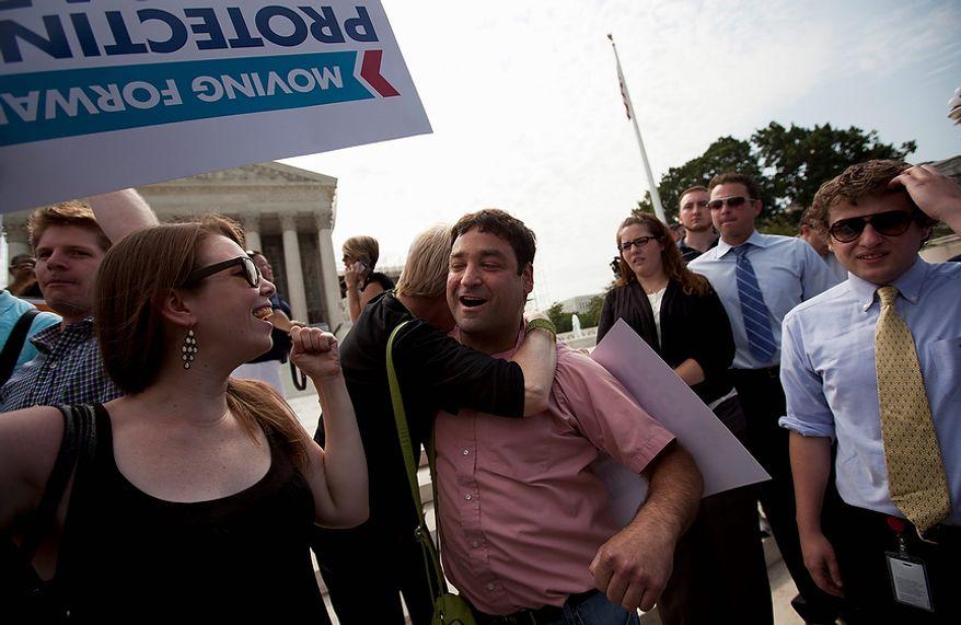 Donny Kirsch of Washington gets a hug as he celebrates the Supreme Court decision on health care, Thursday, June 28, 2012, in Washington.  (AP Photo/Evan Vucci)