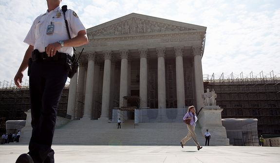 A journalist runs a copy of the Supreme Court decision on health care to her colleagues, Thursday, June 28, 2012, in Washington.  (AP Photo/Evan Vucci)