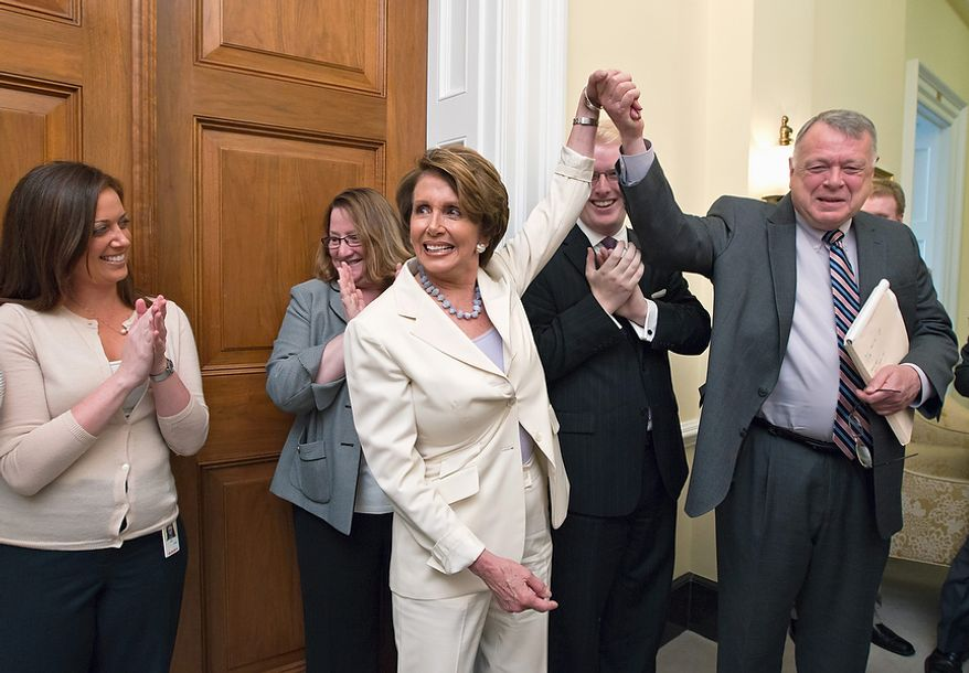 House Minority Leader Nancy Pelosi of Calif. relays the breaking news to her staff that the Supreme Court had just upheld the Affordable Care Act, Thursday, June 28, 2012, on Capitol Hill in Washington. Pelosi, the former speaker of the House, was instrumental in helping to pass health care reform in Congress and was at President Obama's side when he signed it into law. At right, Pelosi gives credit to Wendell Primus, a senior policy adviser. (AP Photo/J. Scott Applewhite)