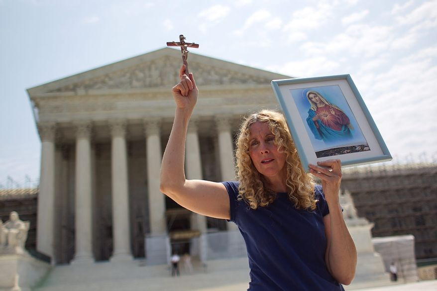Carol Anderson of Williamsburg, Va., holds a cross outside the Supreme Court in Washington, Thursday, June 28, 2012, after the court's ruling on health care.  (AP Photo/Evan Vucci)