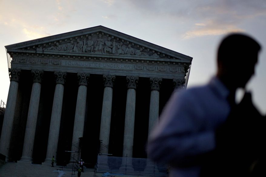 The Supreme Court stands in the background as people gather outside Thursday, June 28, 2012, in Washington. Saving its biggest case for last, the Supreme Court is expected to announce its verdict Thursday on President Barack Obama's health care law. (AP Photo/David Goldman)