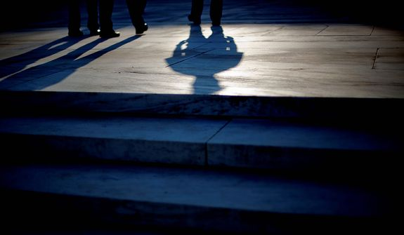 The shadow of an officer is cast as he stands guard on the steps of the Supreme Court in Washington, Thursday, June 28, 2012. Saving its biggest case for last, the Supreme Court is expected to rule on President Barack Obama's health care law. (AP Photo/David Goldman)