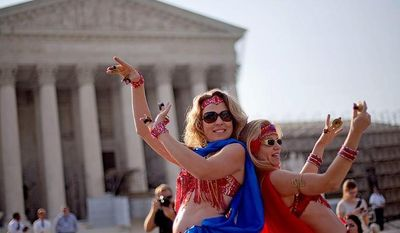 Belly dancers Angela Petry, left, and Jennifer Carpenter-Peak, both of Washington, dance outside the Supreme Court in Washington,Thursday, June 28, 2012, in Washington, as part of a demonstration as the Supreme Court is expected to rule on President Barack Obama's health care law. (AP Photo/David Goldman)