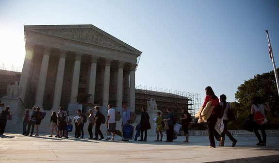 People who waited in line overnight to hear the Supreme Court on a landmark case on health care hold their belongings as they make their way into the court in Washington, Thursday, June 28, 2012.  (AP Photo/Evan Vucci)