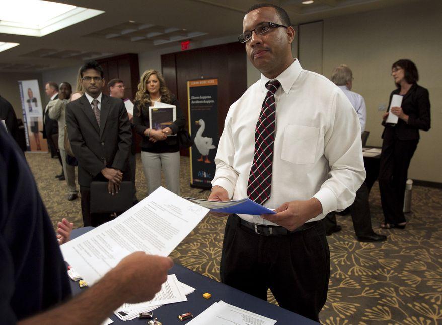 Trey Fortes (right) speaks with Jason Monteiro (left) of Hudson, Mass., during a job fair in Boston on Monday, June 18, 2012. (AP Photo/Steven Senne)