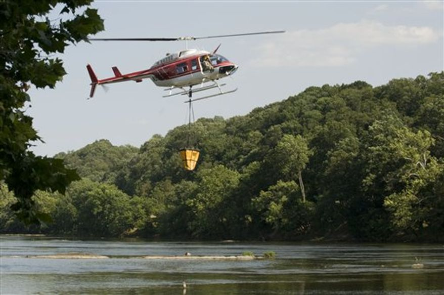 A helicopter prepares to set down to load a ninety gallon bucket of water to help combat this forest fire Wednesday, June 27, 2012 on the Massanutten Mountain between Veach Gap and Sherman Gap in Warren and Shenandoah, Va. counties. (AP Photo/ Northern Virginia Daily, Rich Cooley)
