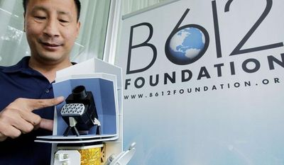 Ed Lu, Chairman of the B612 Foundation, shows a model Thursday of the Sentinel Space Telescope. A group of ex-NASA astronauts and scientists plan to launch the telescope to search for asteroids that may pose a danger to Earth. (Associated Press)