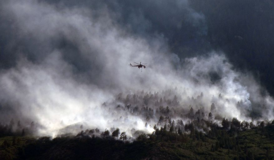 **FILE** A helicopters flies over as the Waldo Canyon fire continues to burn June 27, 2012, in Colorado Springs, Colo. (Associated Press)