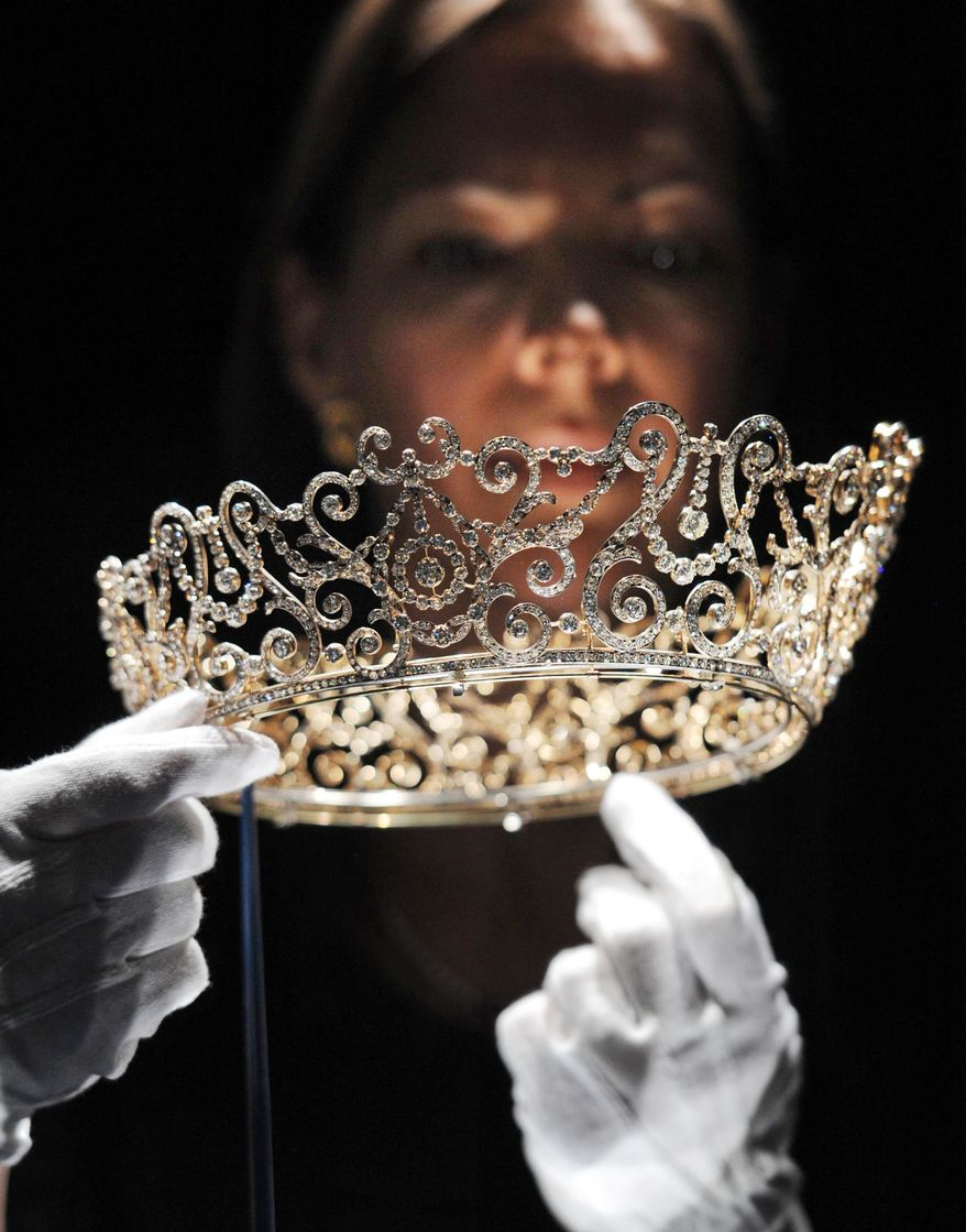 Curator Caroline de Guitaut holds the Delhi Durbar tiara, on show for the first time and made to mark the succession of King George V as King Emperor in 1911, at a new exhibition at Buckingham Palace in London on June 28, 2012. The exhibition shows jewels collected by six monarchs over three centuries to mark the Queen's Diamond jubilee this summer. (Associated Press/Stefan Rousseau/PA Wire)