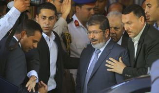 Egypt's President-elect Mohammed Morsi is guarded by presidential security as he leaves Friday prayers at Al-Azhar mosque, in Cairo, Egypt, Friday, June 29, 2012. Mohammed Morsi was declared Egypt's first freely elected president in modern history on Sunday, June 24, 2012. (AP Photo/Amr Nabil)