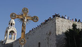 ** FILE ** In this Friday, Dec. 24, 2010, file photo, a cross is seen near the Church of Nativity, traditionally believed by Christians to be the birthplace of Jesus Christ, during a Christmas parade in the West Bank town of Bethlehem. (AP Photo/Nasser Shiyoukhi, File)