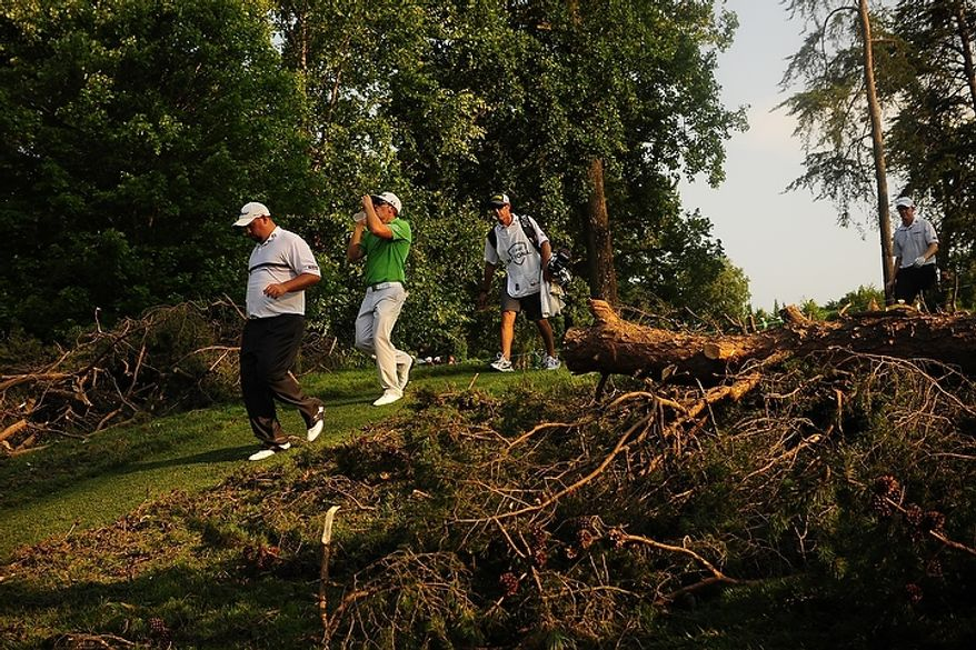 Brendon de Jonge, left, and Hunter Mahan, center, walk through fallen debris at Congressional Country Club during third round play of the AT&T National golf tournament, Bethesda, Md., Saturday, June 30, 2012.  The tournament was closed to the public on Saturday due to storms the previous night causing severe damage throughout the course. (Ryan M.L. Young/The Washington Times)
