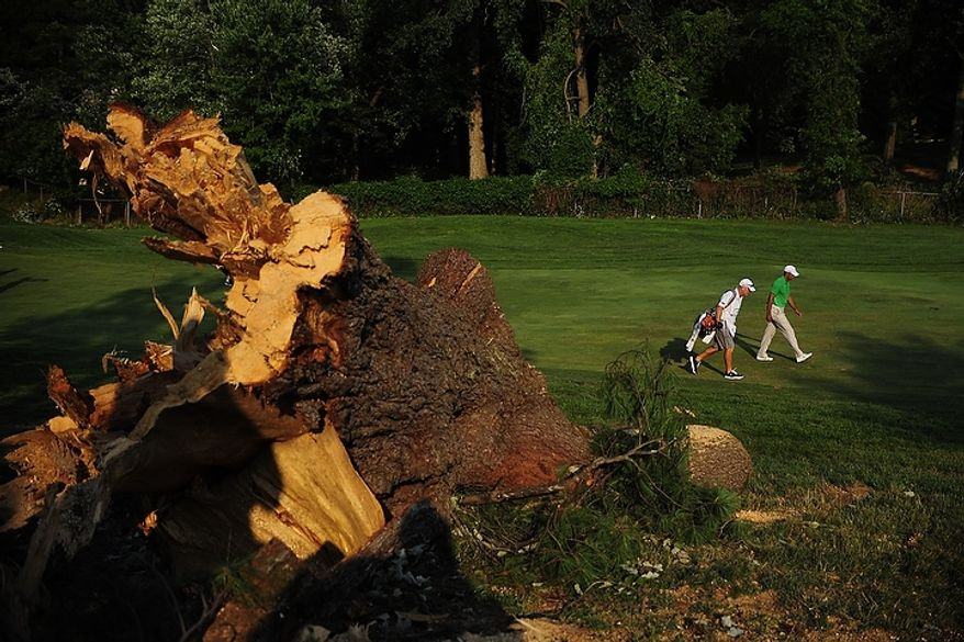 Tiger Woods walks past a broken tree trunk at Congressional Country Club during third round play of the AT&T National golf tournament, Bethesda, Md., Saturday, June 30, 2012.  The tournament was closed to the public on Saturday due to storms the previous night causing severe damage throughout the course.  (Ryan M.L. Young/The Washington Times)