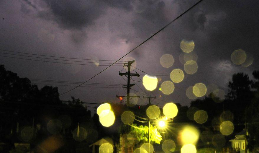 Lightning crackles through the sky above Thornrose Cemetery on Friday, June 29, 2012, in Staunton, Va. (AP Photo/The News Leader, Pat Jarrett)