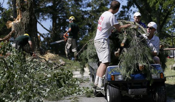 Workers use a golf cart to carry branches from a tree that fell onto the 14th fairway at Congressional Country Club in Bethesda, Md., Saturday, June 30, 2012, after a strong storm blew through overnight. The AT&T National golf tournament was postponed to allow workers to clear the course. (AP Photo/Patrick Semansky)